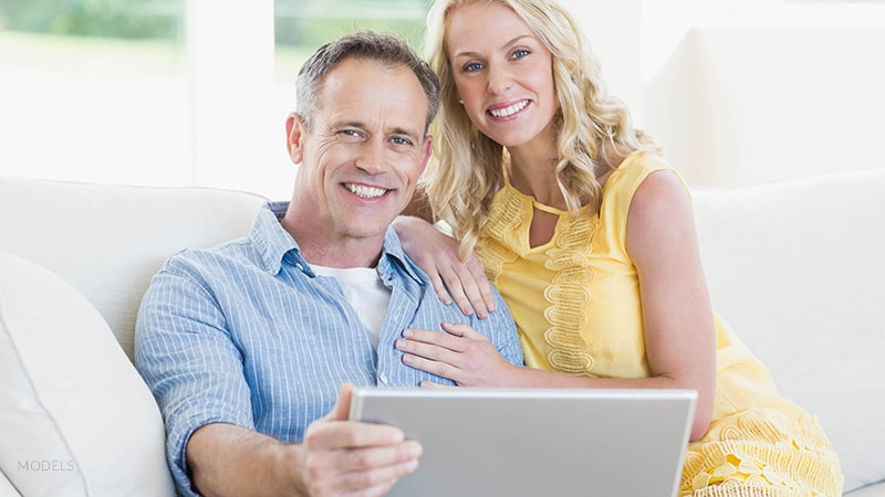 Mature Couple Sitting on Couch With Laptop